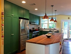 We completely overhauled this kitchen, from the flooring to knocking down a wall and installing new cabinetry, granite countertops, and lighting. We custom-made this island using reclaimed wood from an old barn.