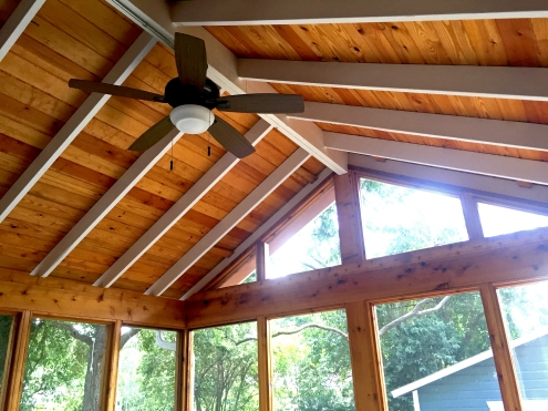 The vaulted ceiling includes wood beams painted white for a finished look. The fan makes the space ideal for hot summer days.